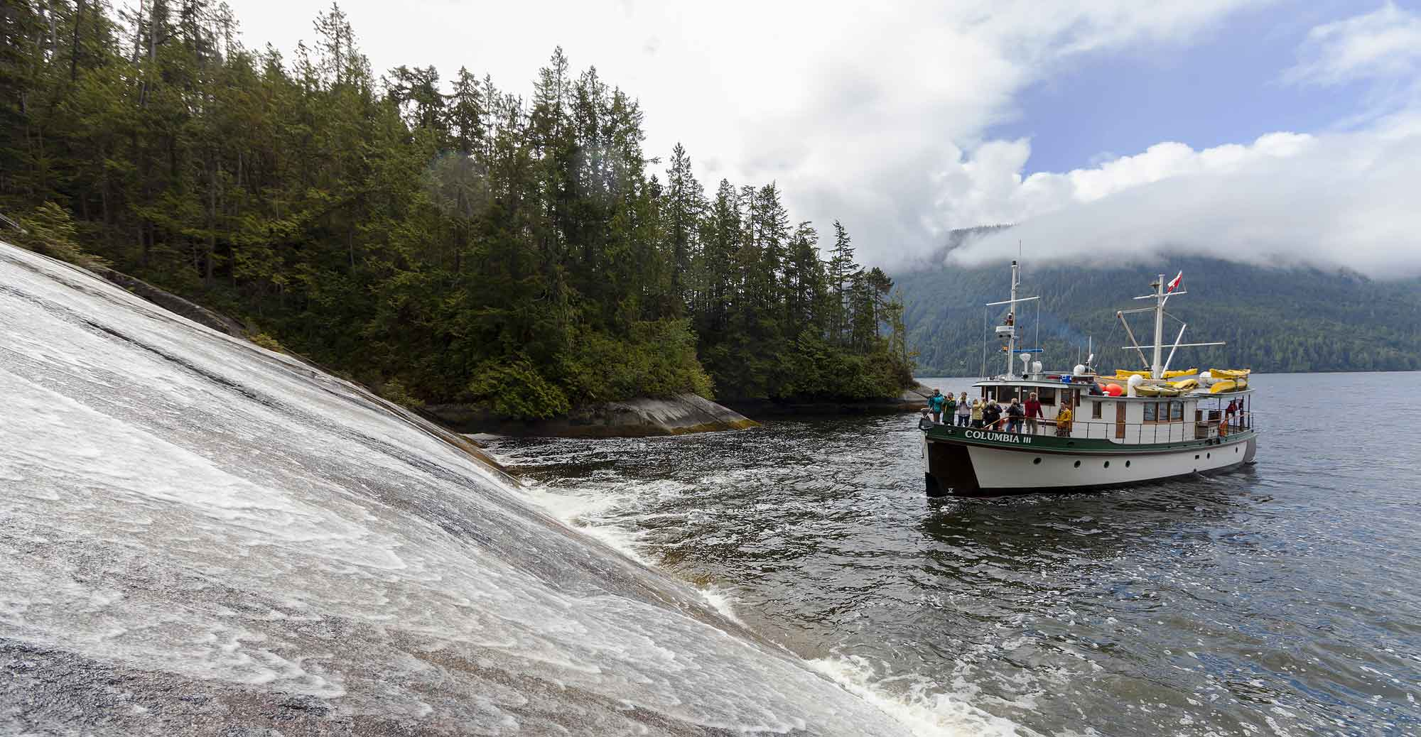 The Columbia III noses into a low angle waterfall in Tribune Channel for guests to take pictures while on a photo-tour in the Broughton Archipelago. Broughton Archipelago, Central British Columbia Coast, British Columbia, Canada.